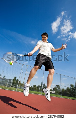 An asian tennis player jumping in the air hitting tennis ball