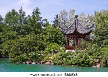 An Asian themed garden and pond on a hot summer's day. - stock photo
