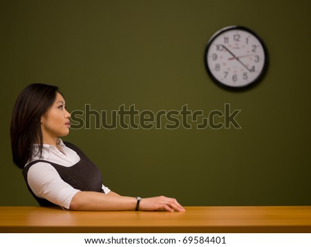An asian woman sitting at a desk watching the clock - stock photo