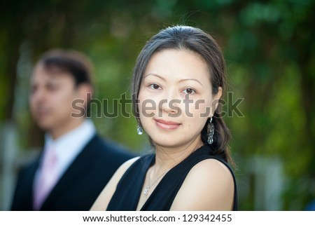 An asian woman smiling in the foreground. - stock photo
