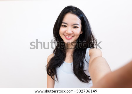 An asian woman taking self portrait isolated on white - stock photo