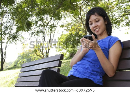 An Asian woman using her cellphone at a park - stock photo