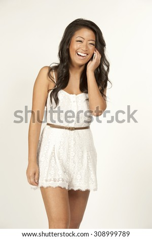 An asian young attractive female wearing a white dress on a white background - smiling and talking on her phone. - stock photo