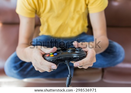 An Asian young man holding game controller playing video games - stock photo