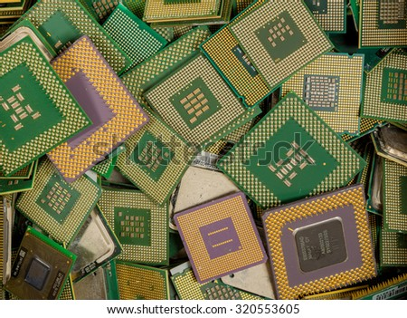 An assorted pile of CPUs. The CPUs were removed from computers for recycling. The pins on most of them are gold plated. - stock photo