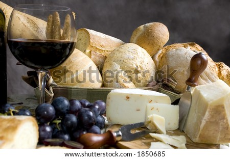 An assortment of breads and cheese with a glass of chianti wine - stock photo