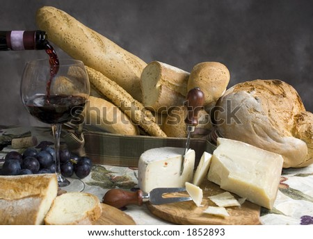 An assortment of breads and cheese with a glass of chianti wine