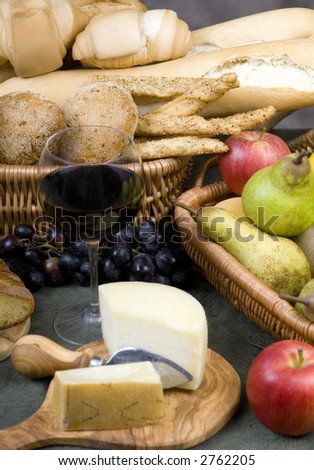 An assortment of breads with a glass of red wine and fruit