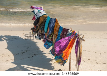 An assortment of brightly colored textiles blowing in the ocean breeze on a pristine beach - stock photo