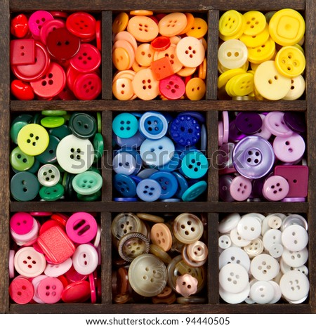 an assortment of buttons in a rainbow of colors, in a printers box - stock photo