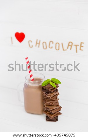 An assortment of dark and milk chocolate with chocolate milkshake and decoration on wooden board. I love chocolate concept - stock photo