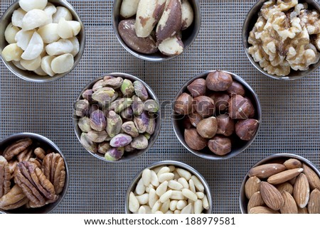 An assortment of eight different kinds of raw nuts in small containers on a screen. - stock photo
