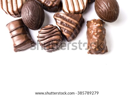 An assortment of fine chocolates in dark, and milk chocolate on white background