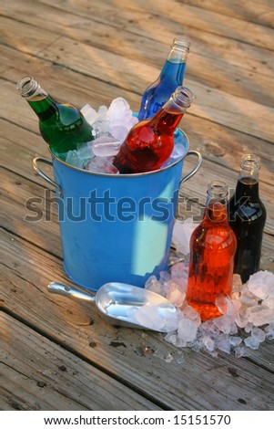 An assortment of flavored sodas in an ice bucket with some on the side and ice that has spilled out onto the deck.