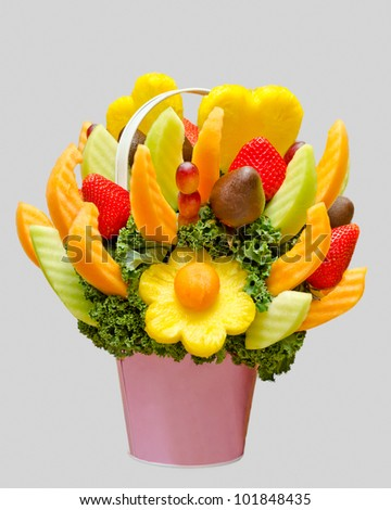 an assortment of fresh fruit in a fruit basket, resembling a flower bouquet isolated on grey background - stock photo