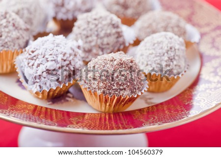 An assortment of homemade Christmas truffles each coated in special toppings. Each in its own foil cup on a special Christmas serving platter. - stock photo