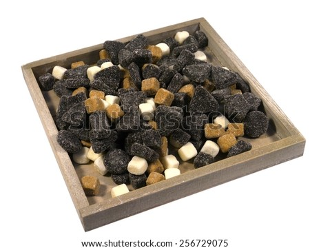 An assortment of liquorice candies in a wooden bowl over white - stock photo