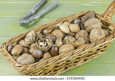 An assortment of nuts in a basket on green wooden table - stock photo
