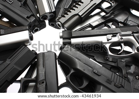 An assortment of pistols on a table. - stock photo