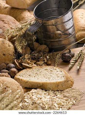 An assortment of whole grain breads with mixed nuts and seeds on a table. An old time sifter sits in the background