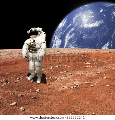 An astronaut looks up at an alien sun that illuminates the barren world he stands on. A large water covered world with clouds rises in the background. - Elements of this image furnished by NASA.