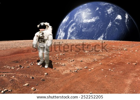 An astronaut surveys his situation after being marooned on a barren planet. A large, water covered world rises above the horizon. - Elements of this image furnished by NASA.