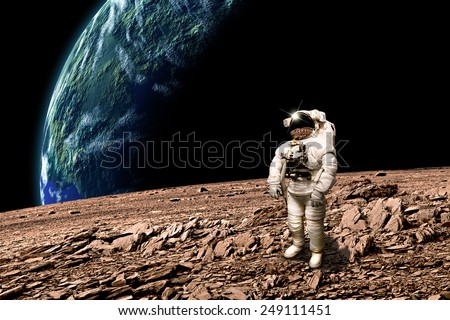 An astronaut surveys his situation after being marooned on a barren planet. An Earth-like planet shines in the background. - Elements of this image furnished by NASA.
