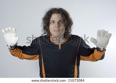 An athlete posing in a goalie stance.  His hands are gloved and he has his arms stretched out defensively. Horizontally framed shot. - stock photo