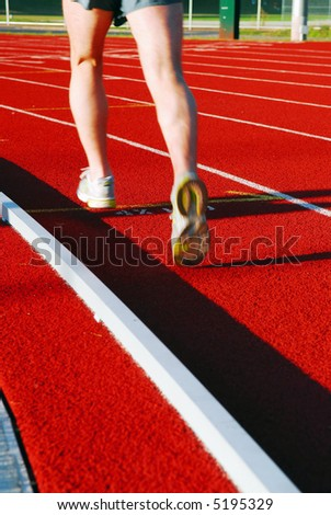 An athlete running on a red racetrack