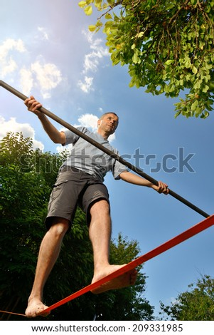 an athlete who is training to walk a tight rope - stock photo