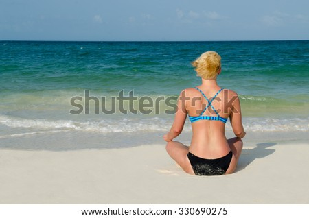 An Athletic Blond Woman Mediates in the White Sand of the Beach at the Cancun Sea - stock photo