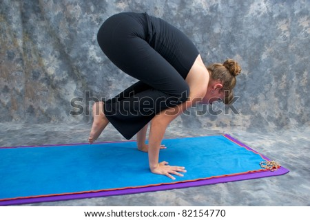 An athletic brown haired woman is balancing in  yoga exercise posture Bakasana or crane crow pose on yoga mat in studio with mottled background. - stock photo