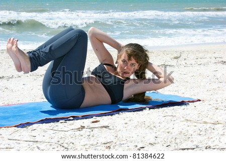 an athletic brown haired woman is doing yoga exercise abdominal crunch on an empty beach at the gulf of mexico in bonita springs florida - stock photo