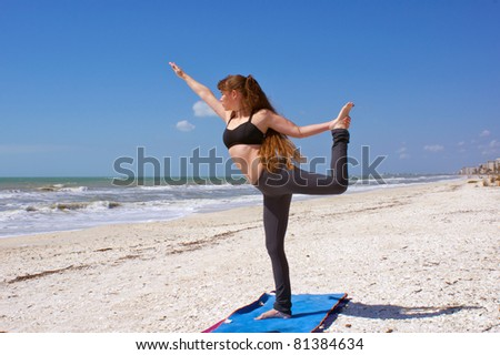 an athletic brown haired woman is doing yoga exercise dancer pose on an empty beach at the gulf of mexico in bonita springs florida