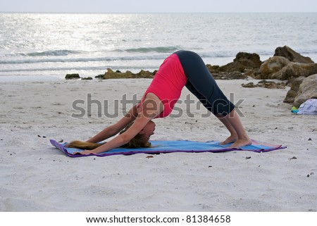 an athletic brown haired woman is doing yoga exercise downward facing dog pose or Adho Mukha Svanasana posture on an empty beach at the gulf of mexico in naples florida at sunset - stock photo