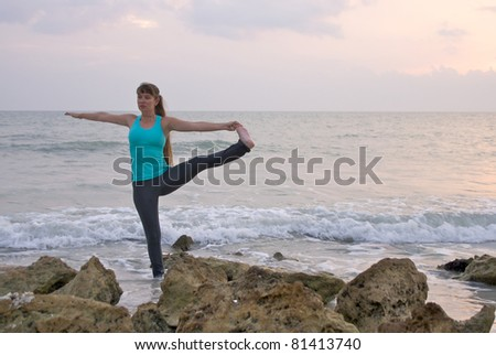 an athletic brown haired woman is doing yoga exercise extended standing hand to toe pose in the ocean water at the gulf of mexico in naples florida at sunset - stock photo