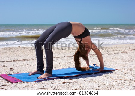 an athletic brown haired woman is doing yoga exercise full wheel pose or Urdhva Dhanurasana also known as upward bow posture on an empty beach at the gulf of mexico in bonita springs florida - stock photo