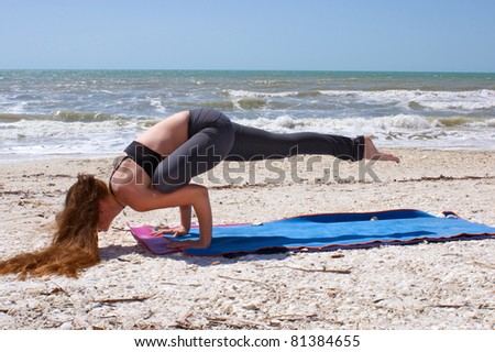 an athletic brown haired woman is doing yoga exercise Galavasana or sage pose on an empty beach at the gulf of mexico in bonita springs florida - stock photo