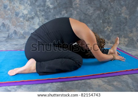 An athletic brown haired woman is doing yoga exercise  Knee to the Head  pose or Janu Sirsasana posture on yoga mat in studio with mottled background. - stock photo