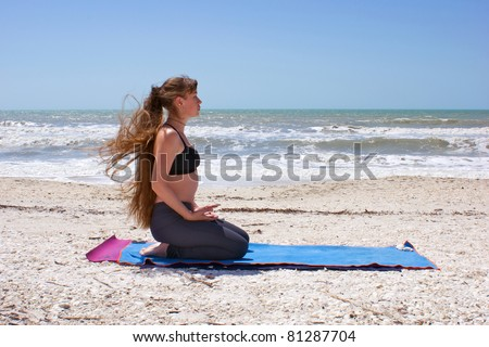 an athletic brown haired woman is doing yoga exercise on an empty beach Virasana or hero pose at the gulf of mexico in bonita springs florida with long hair blowing in wind - stock photo