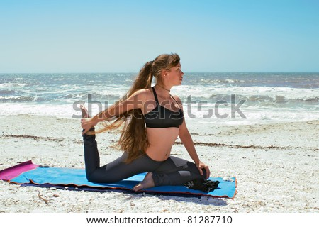 an athletic brown haired woman is doing yoga exercise  on beach in Kapotasana or King Pigeon Pose on an empty beach at the gulf of mexico in bonita springs florida with long hair blowing in wind - stock photo