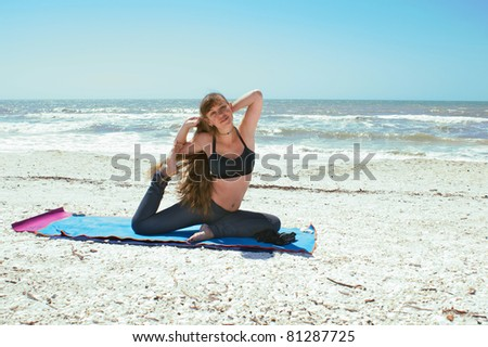 an athletic brown haired woman is doing yoga exercise on beach in Kapotasana or Pigeon Pose on an empty beach at the gulf of mexico in bonita springs florida with long hair blowing in wind - stock photo