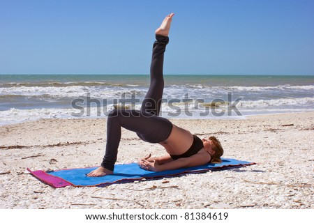 an athletic brown haired woman is doing yoga exercise one leg bridge pose on an empty beach at the gulf of mexico in bonita springs florida - stock photo