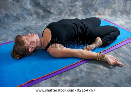 An athletic brown haired woman is doing yoga exercise Reclined hero posture on yoga mat in studio with mottled background.