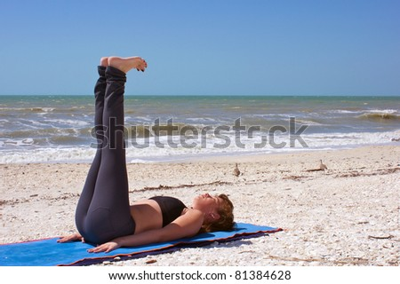 an athletic brown haired woman is doing yoga exercise reclined staff pose on an empty beach at the gulf of mexico in bonita springs florida - stock photo