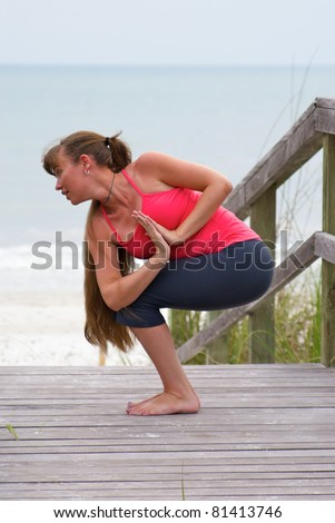 an athletic brown haired woman is doing yoga exercise rotated awkward chair pose on an empty beach at the gulf of mexico in naples florida at sunset - stock photo