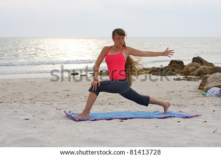 an athletic brown haired woman is doing yoga exercise rotated high lunge pose on an empty beach at the gulf of mexico in naples florida at sunset - stock photo