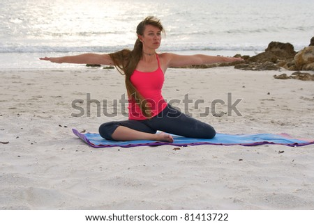 an athletic brown haired woman is doing yoga exercise seated warrior 2 pose on an empty beach at the gulf of mexico in naples florida at sunset - stock photo