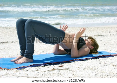an athletic brown haired woman is doing yoga exercise  Setu Bandhasanasana or bridge pose on an empty beach at the gulf of mexico in bonita springs florida - stock photo