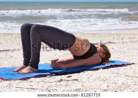 an athletic brown haired woman is doing yoga exercise  Setu Bandhasanasana or bridge pose on an empty beach at the gulf of mexico in bonita springs florida